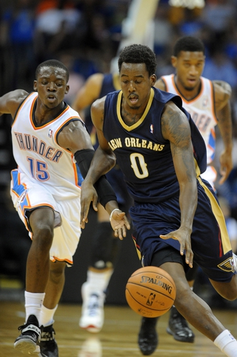 Oct 17, 2013; Tulsa, OK, USA; New Orleans Pelicans small forward Al-Farouq Aminu (0) handles the ball against Oklahoma City Thunder point guard Reggie Jackson (15) during the third quarter at BOK Center. Mandatory Credit: Mark D. Smith-USA TODAY Sports