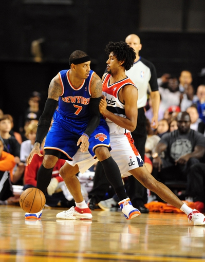 Oct 17, 2013; Baltimore, MD, USA; New York Knicks forward Carmelo Anthony (7) is defended by Washington Wizards forward Josh Childress (8) at Baltimore Arena. Mandatory Credit: Evan Habeeb-USA TODAY Sports