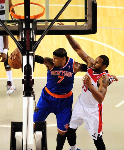 Oct 17, 2013; Baltimore, MD, USA; New York Knicks forward Carmelo Anthony (7) grabs a rebound in front of Washington Wizards forward Trevor Booker (35) at Baltimore Arena. Mandatory Credit: Evan Habeeb-USA TODAY Sports