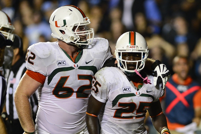 Oct 17, 2013; Chapel Hill, NC, USA; Miami Hurricanes running back Dallas Crawford (25) reacts with offensive linesman Shane McDermott (62) after scoring the winning touchdown in the fourth quarter. The Miami Hurricanes defeated the North Carolina Tar Heels 27-23 at Kenan Memorial Stadium. Mandatory Credit: Bob Donnan-USA TODAY Sports