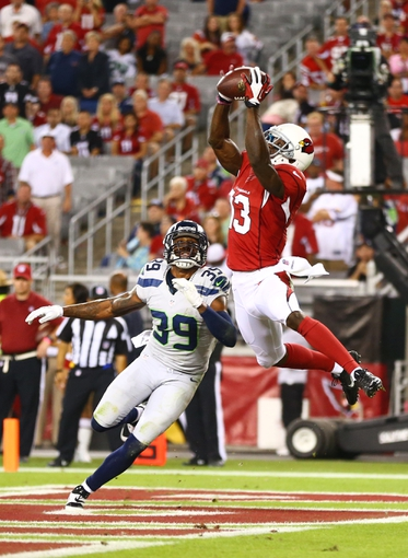 Oct 17, 2013; Phoenix, AZ, USA; Arizona Cardinals wide receiver Jaron Brown (13) catches a pass for a touchdown under pressure from Seattle Seahawks cornerback Brandon Browner in the fourth quarter at University of Phoenix Stadium. Mandatory Credit: Mark J. Rebilas-USA TODAY Sports