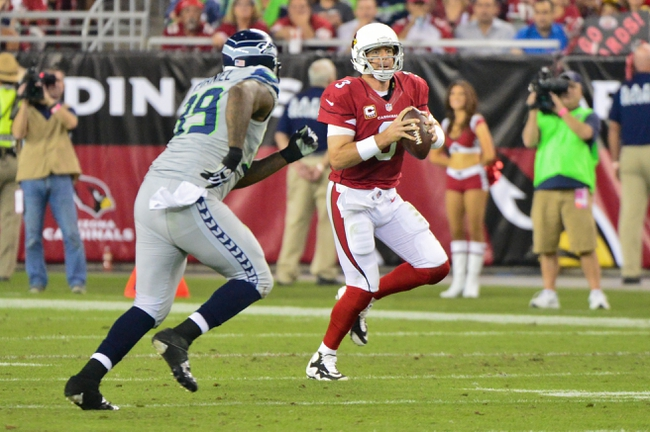 Oct 17, 2013; Phoenix, AZ, USA; Arizona Cardinals quarterback Carson Palmer (3) runs from Seattle Seahawks defensive tackle Tony McDaniel (99) during the second half at University of Phoenix Stadium. Mandatory Credit: Matt Kartozian-USA TODAY Sports