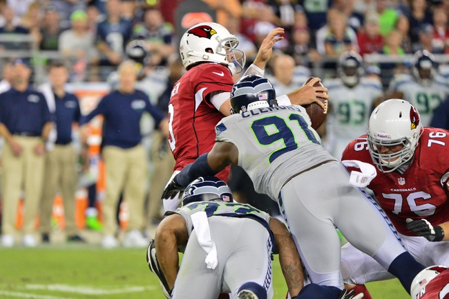 Oct 17, 2013; Phoenix, AZ, USA; Arizona Cardinals quarterback Carson Palmer (3) is sacked by Seattle Seahawks defensive end Chris Clemons (91) and defensive end Michael Bennett (72) during the second half at University of Phoenix Stadium. Mandatory Credit: Matt Kartozian-USA TODAY Sports
