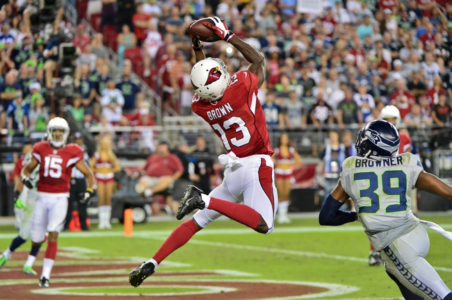 Oct 17, 2013; Phoenix, AZ, USA; Arizona Cardinals wide receiver Jaron Brown (13) catches an eight yard touchdown during the second half as Seattle Seahawks cornerback Brandon Browner (39) defends at University of Phoenix Stadium. Mandatory Credit: Matt Kartozian-USA TODAY Sports