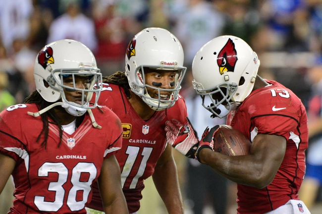 Arizona Cardinals wide receiver Jaron Brown (13) celebrates with wide receiver Larry Fitzgerald (11) and running back Andre Ellington (38) after catching an eight yard touchdown during the second half against the Seattle Seahawks at University of Phoenix Stadium. Mandatory Credit: Matt Kartozian-USA TODAY Sports