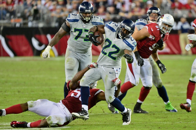 Oct 17, 2013; Phoenix, AZ, USA; Seattle Seahawks running back Robert Turbin (22) breaks a tackle by Arizona Cardinals inside linebacker Karlos Dansby (56) during the second half at University of Phoenix Stadium. Mandatory Credit: Matt Kartozian-USA TODAY Sports