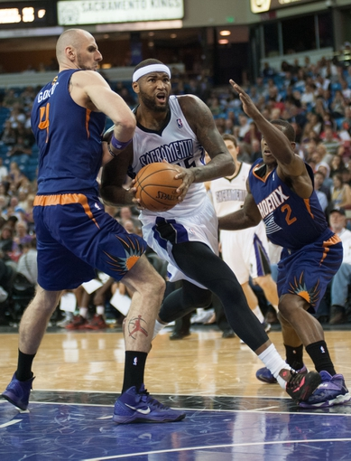 Oct 17, 2013; Sacramento, CA, USA; Sacramento Kings center DeMarcus Cousins (15) drives to the basket against Phoenix Suns center Marcin Gortat (4) during the third quarter at Sleep Train Arena. The Sacramento Kings defeated the Phoenix Suns 107-90 Mandatory Credit: Ed Szczepanski-USA TODAY Sports