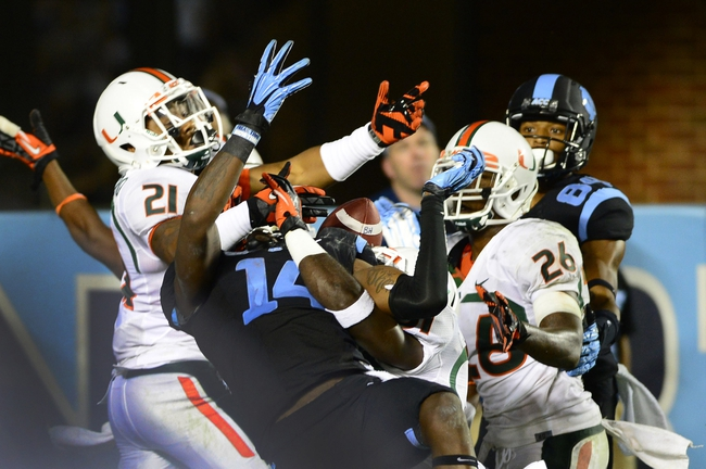 Oct 17, 2013; Chapel Hill, NC, USA; Miami Hurricanes defensive back Antonio Crawford (21) and linebacker Tyrone Cornileus (31) and defensive back Rayshawn Jenkins (26) break up a pass in the end zone intended for North Carolina Tar Heels wide receiver Quinshad Davis (14) on the last play of the game. The Miami Hurricanes defeated the North Carolina Tar Heels 27-23 at Kenan Memorial Stadium. Mandatory Credit: Bob Donnan-USA TODAY Sports