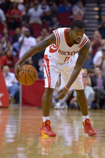 Oct 16, 2013; Houston, TX, USA; Houston Rockets point guard Aaron Brooks (0) dribbles against the Orlando Magic during the second half at Toyota Center. The Rockets won 108-104. Mandatory Credit: Thomas Campbell-USA TODAY Sports