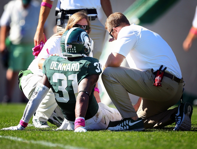 Oct 12, 2013; East Lansing, MI, USA; Michigan State Spartans trainers check on cornerback Darqueze Dennard (31) during the second half in a game at Spartan Stadium. MSU won 42-28. Mandatory Credit: Mike Carter-USA TODAY Sports