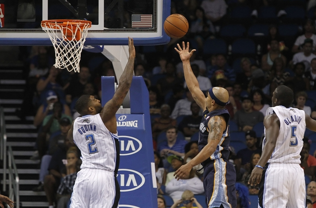 Oct 18, 2013; Orlando, FL, USA; Memphis Grizzlies point guard Jerryd Bayless (7) shoots over Orlando Magic power forward Kyle O'Quinn (2) during the second half at Amway Center. Memphis Grizzlies defeated the Orlando Magic 97-91. Mandatory Credit: Kim Klement-USA TODAY Sports