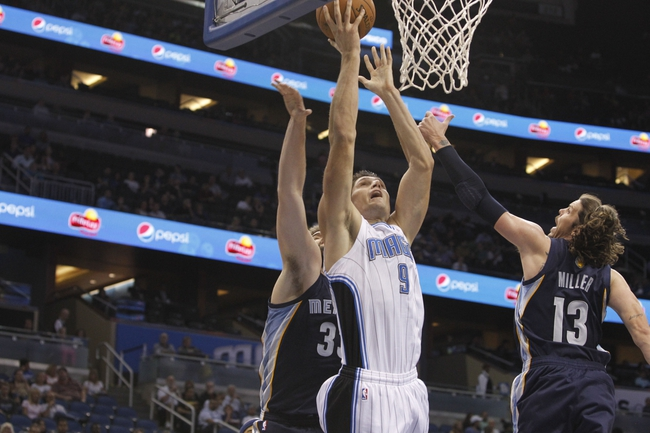 Oct 18, 2013; Orlando, FL, USA; Orlando Magic center Nikola Vucevic (9) shoots as Memphis Grizzlies center Marc Gasol (33) and small forward Mike Miller (13) defends during the second half at Amway Center. Memphis Grizzlies defeated the Orlando Magic 97-91. Mandatory Credit: Kim Klement-USA TODAY Sports