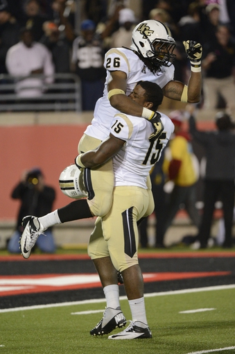Oct 18, 2013; Louisville, KY, USA; UCF Knights defensive back Clayton Geathers (26) celebrates with linebacker Michael Easton (15) after defeating the Louisville Cardinals in the second half of play at Papa John's Cardinal Stadium. Central Florida defeated Louisville 38-35.  Mandatory Credit: Jamie Rhodes-USA TODAY Sports
