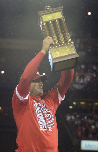Oct 18, 2013; St. Louis, MO, USA; St. Louis Cardinals manager Mike Matheny hoists National League championship trophy after game six of the National League Championship Series baseball game against the Los Angeles Dodgers at Busch Stadium. Mandatory Credit: Jeff Curry-USA TODAY Sports