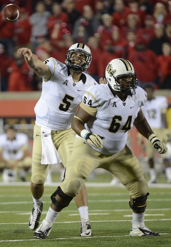 Oct 18, 2013; Louisville, KY, USA; UCF Knights quarterback Blake Bortles (5) throws a pass under the protection of offensive linesman Justin McCray (64) during the second half of play against the Louisville Cardinals at Papa John's Cardinal Stadium. Central Florida defeated Louisville 38-35.  Mandatory Credit: Jamie Rhodes-USA TODAY Sports