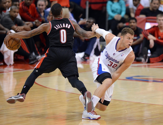 Oct 18, 2013; Los Angeles, CA, USA;  Portland Trail Blazers point guard Damian Lillard (0) is fouled by Los Angeles Clippers power forward Blake Griffin (32) in the second quarter of the game at the Staples Center. Mandatory Credit: Jayne Kamin-Oncea-USA TODAY Sports