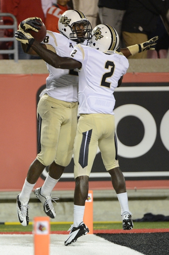 Oct 18, 2013; Louisville, KY, USA; UCF Knights running back William Stanback (28) celebrates with UCF Knights wide receiver Jeff Godfrey (2) after scoring a touch down against the Louisville Cardinals during the second half of play at Papa John's Cardinal Stadium. Central Florida defeated Louisville 38-35.  Mandatory Credit: Jamie Rhodes-USA TODAY Sports