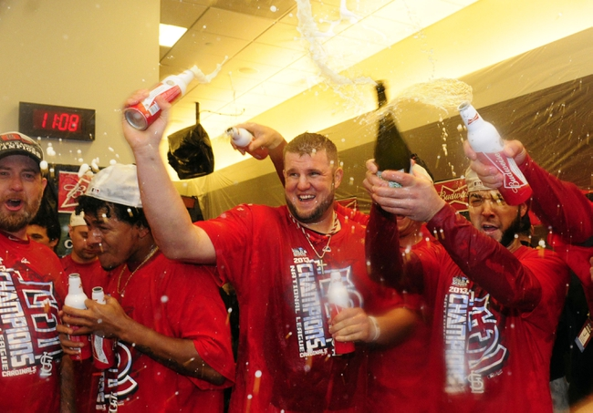 Oct 18, 2013; St. Louis, MO, USA; St. Louis Cardinals players Carlos Martinez (left) , Matt Adams (middle) and Tony Cruz celebrate in the clubhouse after game six of the National League Championship Series baseball game against the Los Angeles Dodgers at Busch Stadium. Mandatory Credit: Jeff Curry-USA TODAY Sports