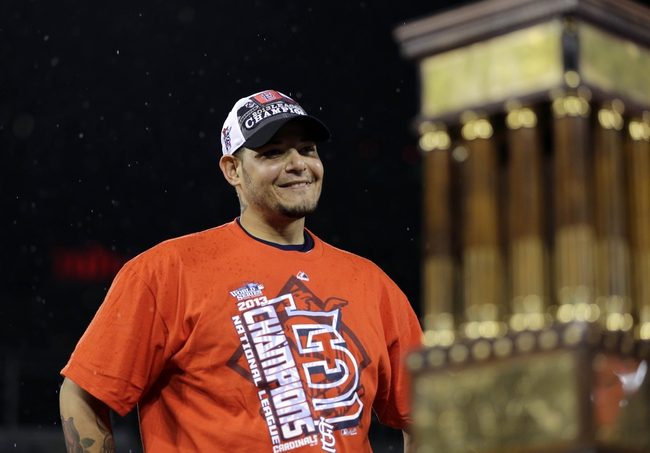 Oct 18, 2013; St. Louis, MO, USA; St. Louis Cardinals catcher Yadier Molina celebrates next to the National League championship trophy after game six of the National League Championship Series baseball game against the Los Angeles Dodgers at Busch Stadium. Mandatory Credit: David J. Phillip/Pool Photo via USA TODAY Sports