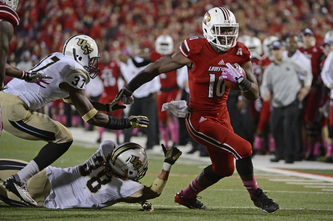 Oct 18, 2013; Louisville, KY, USA; Louisville Cardinals running back Dominique Brown (10)  evades the tackle of UCF Knights defensive back Jordan Ozerities (38) and defensive back Brandon Alexander (37) to score a touch down during the second half of play at Papa John's Cardinal Stadium. Central Florida defeated Louisville 38-35.  Mandatory Credit: Jamie Rhodes-USA TODAY Sports
