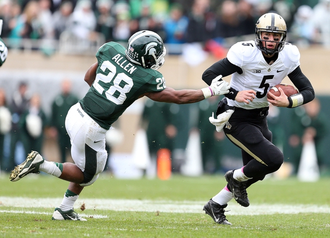 Oct 19, 2013; East Lansing, MI, USA; Purdue Boilermakers quarterback Danny Etling (5) scrambles out of the pocket against Michigan State Spartans linebacker Denicos Allen (28) during the 1st quarter at Spartan Stadium. Mandatory Credit: Mike Carter-USA TODAY Sports