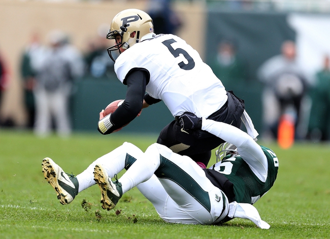Oct 19, 2013; East Lansing, MI, USA; Purdue Boilermakers quarterback Danny Etling (5) is sacked by Michigan State Spartans safety RJ Williamson (26) during the 1st quarter at Spartan Stadium. Mandatory Credit: Mike Carter-USA TODAY Sports