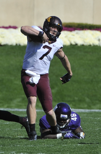 Oct 19, 2013; Evanston, IL, USA; Minnesota Golden Gophers quarterback Mitch Leidner (7) escapes a tackle by Northwestern Wildcats linebacker Damien Proby (46) during the first quarter at Ryan Field. Mandatory Credit: David Banks-USA TODAY Sports
