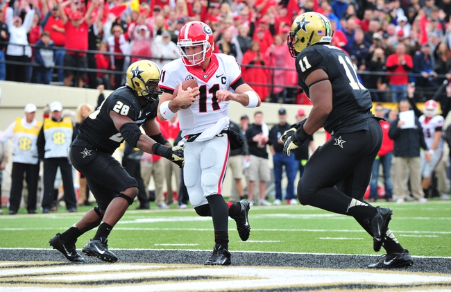 Oct 19, 2013; Nashville, TN, USA; Georgia Bulldogs quarterback Aaron Murray (11) runs for a touchdown against Vanderbilt Commodores linebacker Karl Butler (28) and linebacker Harding Harper (11) during the first half at Vanderbilt Stadium. Mandatory Credit: Don McPeak-USA TODAY Sports