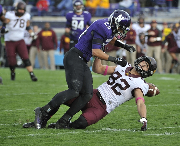Oct 19, 2013; Evanston, IL, USA;  Minnesota Golden Gophers wide receiver Drew Wolitarsky (82) is defended by Northwestern Wildcats cornerback Nick VanHoose (23) during the second half at Ryan Field.  The Minnesota Golden Gophers defeated the Northwestern Wildcats 20-17. Mandatory Credit: David Banks-USA TODAY Sports
