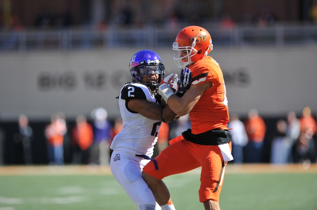 Oct 19, 2013; Stillwater, OK, USA; Oklahoma State Cowboys wide receiver Charlie Moore (17) fights for the ball against Texas Christian Horned Frogs safety Jason Verrett (2) during the first half at Boone Pickens Stadium. Mandatory Credit: Peter G. Aiken-USA TODAY Sports