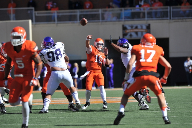 Oct 19, 2013; Stillwater, OK, USA; Oklahoma State Cowboys quarterback Clint Chelf (10) throws a pass down field against the Texas Christian Horned Frogs during the first half at Boone Pickens Stadium. Mandatory Credit: Peter G. Aiken-USA TODAY Sports