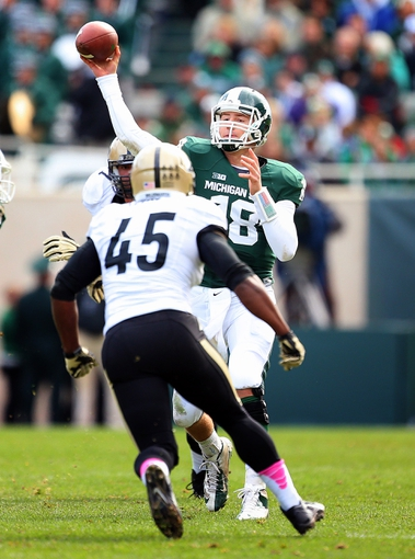 Oct 19, 2013; East Lansing, MI, USA; Michigan State Spartans quarterback Connor Cook (18) passes the ball against Purdue Boilermakers linebacker Will Lucas (45) during the 2nd half at Spartan Stadium. MSU won 14-0. Mandatory Credit: Mike Carter-USA TODAY Sports
