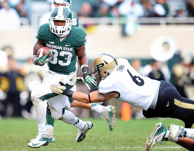 Oct 19, 2013; East Lansing, MI, USA; Michigan State Spartans running back Jeremy Langford (33) runs though the tackle of Purdue Boilermakers linebacker Ruben Ibarra (6) during the 2nd half at Spartan Stadium. MSU won 14-0. Mandatory Credit: Mike Carter-USA TODAY Sports
