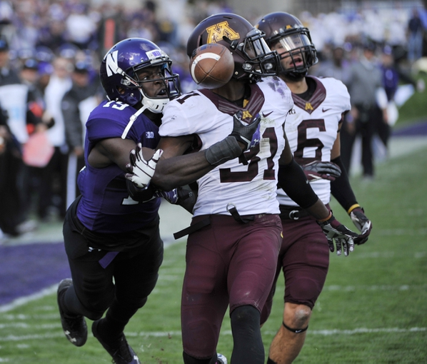 Oct 19, 2013; Evanston, IL, USA; Northwestern Wildcats wide receiver Cameron Dickerson (19) is defended by Minnesota Golden Gophers defensive back Eric Murray (31) during the second half at Ryan Field.  The Minnesota Golden Gophers defeated the Northwestern Wildcats 20-17. Mandatory Credit: David Banks-USA TODAY Sports