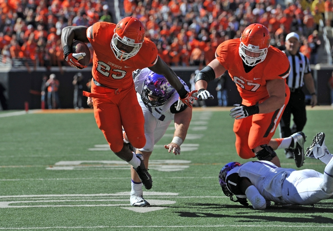 Oct 19, 2013; Stillwater, OK, USA; Oklahoma State Cowboys running back Rennie Childs (23) breaks away from Texas Christian Horned Frogs defensive end Jon Koontz (97) for a seven yard touchdown run during the second half at Boone Pickens Stadium. Oklahoma State won 24-10. Mandatory Credit: Peter G. Aiken-USA TODAY Sports
