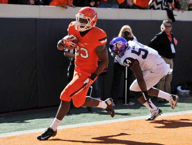 Oct 19, 2013; Stillwater, OK, USA; Oklahoma State Cowboys running back Rennie Childs (23) rushes in past Texas Christian Horned Frogs linebacker Marcus Mallet (54) for a seven yard touchdown during the second half at Boone Pickens Stadium. Oklahoma State won 24-10. Mandatory Credit: Peter G. Aiken-USA TODAY Sports