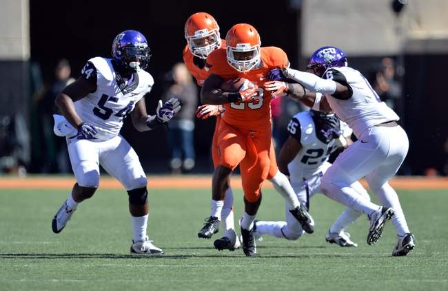 Oct 19, 2013; Stillwater, OK, USA; Oklahoma State Cowboys running back Rennie Childs (23) rushes through Texas Christian Horned Frogs defenders Elisha Olabode (6) and Marcus Mallet  (54) during the second half at Boone Pickens Stadium. Oklahoma State won 24-10. Mandatory Credit: Peter G. Aiken-USA TODAY Sports