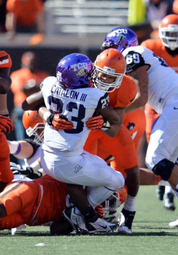 Oct 19, 2013; Stillwater, OK, USA; Oklahoma State Cowboys safety Lyndell Johnson (27) tackles Texas Christian Horned Frogs running back B.J. Catalon (23) for a loss during the second half at Boone Pickens Stadium. Oklahoma State won 24-10. Mandatory Credit: Peter G. Aiken-USA TODAY Sports