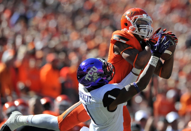 Oct 19, 2013; Stillwater, OK, USA; Oklahoma State Cowboys wide receiver Josh Stewart (5) pulls in a pass against Texas Christian Horned Frogs safety Chris Hackett (1) during the second half at Boone Pickens Stadium. Oklahoma State won 24-10. Mandatory Credit: Peter G. Aiken-USA TODAY Sports