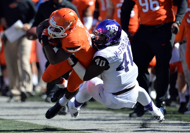 Oct 19, 2013; Stillwater, OK, USA; Texas Christian Horned Frogs defensive end James McFarland (40) tackles Oklahoma State Cowboys running back Rennie Childs (23) along the sideline during the second half at Boone Pickens Stadium. Oklahoma State won 24-10. Mandatory Credit: Peter G. Aiken-USA TODAY Sports