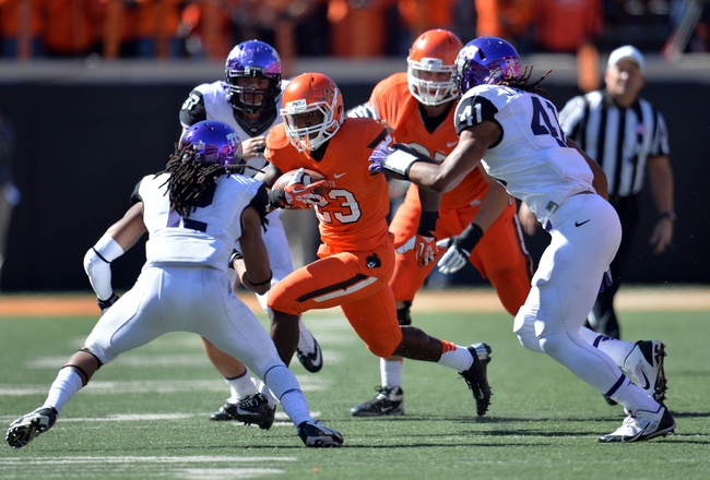 Oct 19, 2013; Stillwater, OK, USA; Oklahoma State Cowboys running back Rennie Childs (23) rushes against Texas Christian Horned Frogs defenders Jonathan Anderson (41) and Jason Verrett (2) during the second half at Boone Pickens Stadium. Oklahoma State won 24-10. Mandatory Credit: Peter G. Aiken-USA TODAY Sports