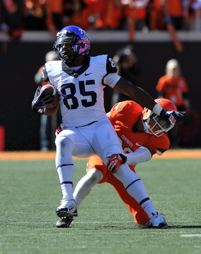 Oct 19, 2013; Stillwater, OK, USA; Texas Christian Horned Frogs wide receiver LaDarius Brown (85) turns up field against pressure from Oklahoma State Cowboys defensive back Tyler Patmon (26) during the second half at Boone Pickens Stadium. Oklahoma State won 24-10. Mandatory Credit: Peter G. Aiken-USA TODAY Sports