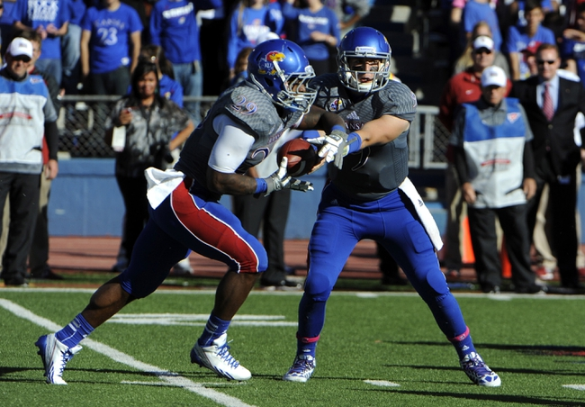 Oct 19, 2013; Lawrence, KS, USA; Kansas Jayhawks quarterback Jake Heaps (9) hands off to running back James Sims (29) against the Oklahoma Sooners in the first half at Memorial Stadium. Mandatory Credit: John Rieger-USA TODAY Sports