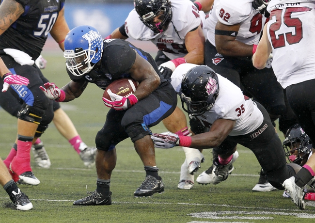 Oct 19, 2013; Buffalo, NY, USA; Massachusetts Minutemen defensive lineman Stanley Andre (35) tries to tackle Buffalo Bulls running back Branden Oliver (32) during the first half at University of Buffalo Stadium. Mandatory Credit: Timothy T. Ludwig-USA TODAY Sports