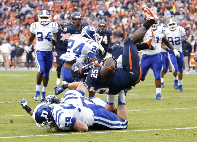 Oct 19, 2013; Charlottesville, VA, USA;  Virginia Cavaliers running back Kevin Parks (25) flips into the end zone to score a touchdown after being hit by Duke Blue Devils linebacker Kelby Brown (59) in the second quarter at Scott Stadium. Mandatory Credit: Geoff Burke-USA TODAY Sports