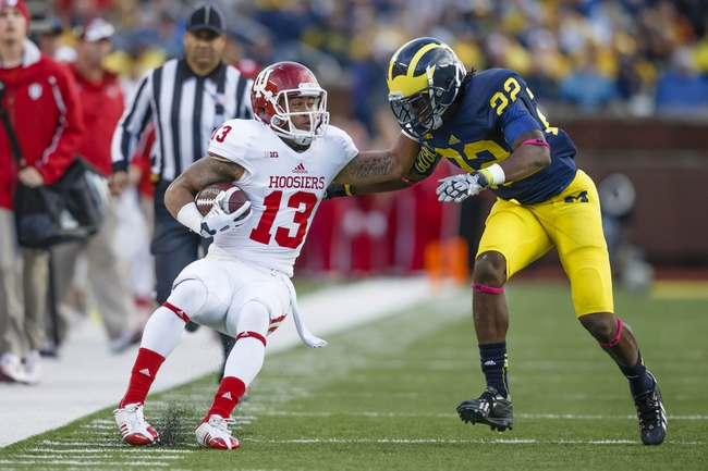 Oct 19, 2013; Ann Arbor, MI, USA; Indiana Hoosiers wide receiver Kofi Hughes (13) runs the ball as Michigan Wolverines safety Jarrod Wilson (22) goes in to tackle in the third quarter at Michigan Stadium. Mandatory Credit: Rick Osentoski-USA TODAY Sports