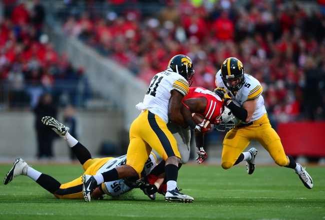 Oct 19, 2013; Columbus, OH, USA; Ohio State Buckeyes running back Carlos Hyde (34) is tackled by Iowa Hawkeyes defensive back Tanner Miller (5) and linebacker Anthony Hitchens (31) during the fourth quarter at Ohio Stadium. Mandatory Credit: Andrew Weber-USA TODAY Sports
