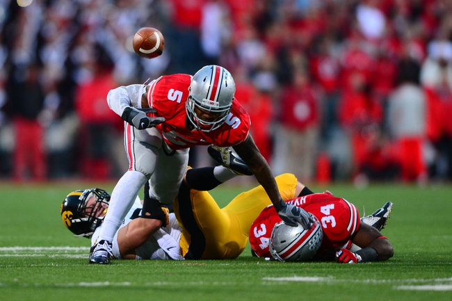 Oct 19, 2013; Columbus, OH, USA; Ohio State Buckeyes quarterback Braxton Miller (5) jumps over Iowa Hawkeyes defensive back Tanner Miller (5) and losses control of the ball during the fourth quarter against at Ohio Stadium. Mandatory Credit: Andrew Weber-USA TODAY Sports
