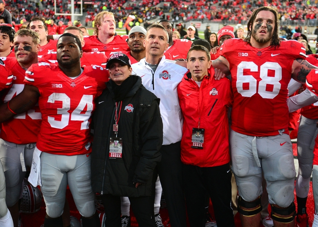 Oct 19, 2013; Columbus, OH, USA; Ohio State Buckeyes running back Carlos Hyde (34), Shelley Meyer and Urban Meyer celebrate after defeating Iowa Hawkeyes 34-24 at Ohio Stadium. Mandatory Credit: Andrew Weber-USA TODAY Sports