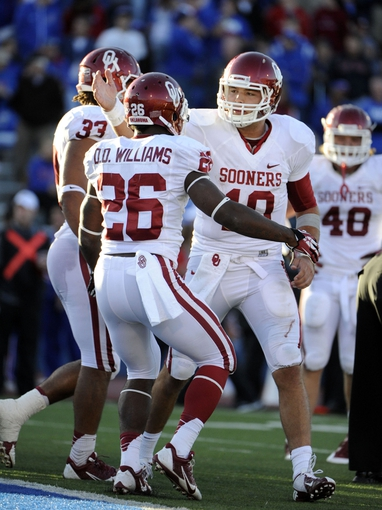 Oct 19, 2013; Lawrence, KS, USA; Oklahoma Sooners running back Damien Williams (26) celebrates with quarterback Blake Bell (10) after scoring a touchdown against the Kansas Jayhawks in the second half at Memorial Stadium. Oklahoma won the game 34-19. Mandatory Credit: John Rieger-USA TODAY Sports